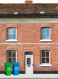 A red brick town house with a white door. There is a green and blue bin to the left of the door.