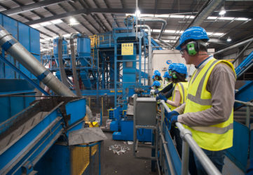 A group inside the Materials Recovery Facility looking at the candensor machine. The people are wearing hard hats, hi vis vests, safety glasses, gloves and headphones.