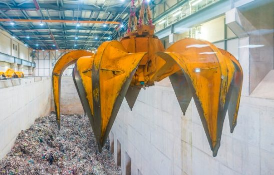 A grabber hanging over a pit of general waste