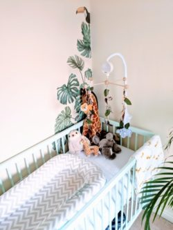 Mint green nursery cot with sleepyhead and animal mobile