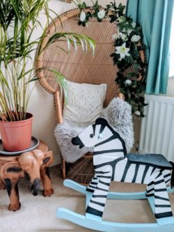 Upcycled wooden rocking zebra in baby nursery with wicker chair and plant