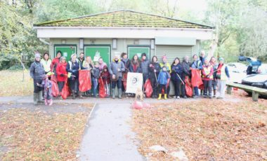 Group of people with litter picks and bags in a park