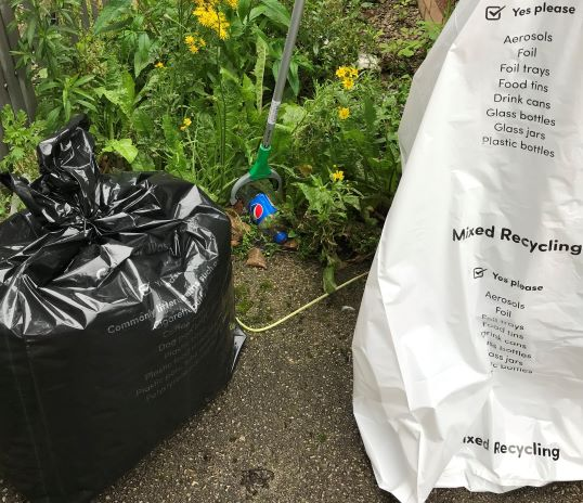 Litter picking a plastic bottle with collection bag