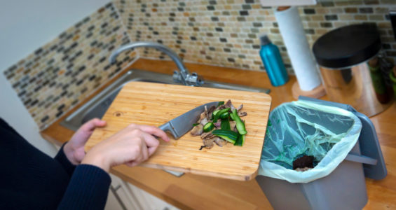 A person scrapping food waste into a kitchen caddy