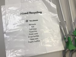white bag for collecting mixed recycling items and three litter pickers