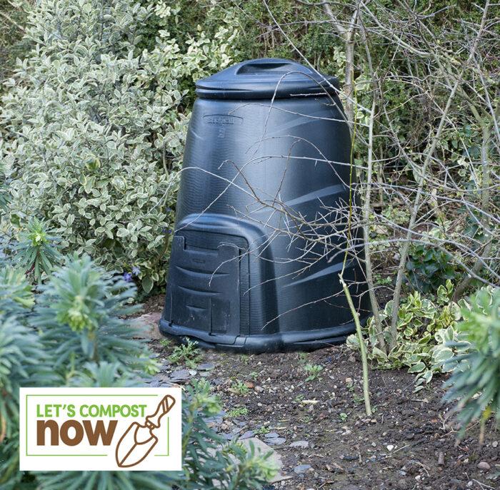 Compost bin in garden shrubbery