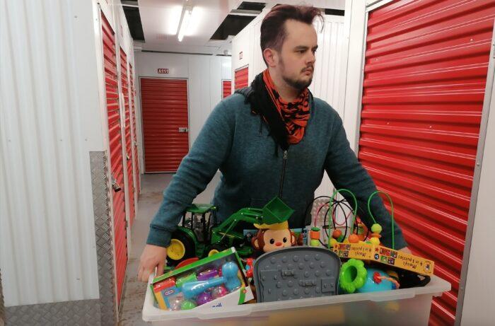 Man holding box full of childrens' toys
