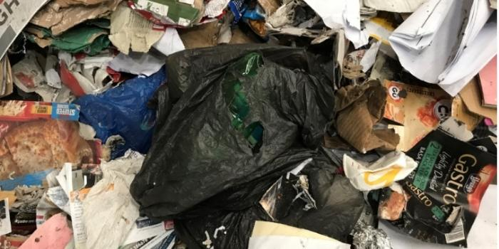 Rubbish bag of waste mixed in with paper and card
