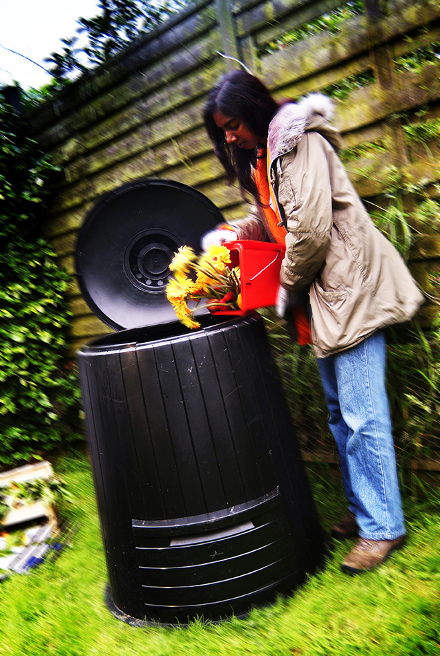 Woman composting old flowers in a home composting bin