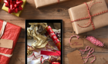 Christmas presents and tablet showing wrapping paper on screen